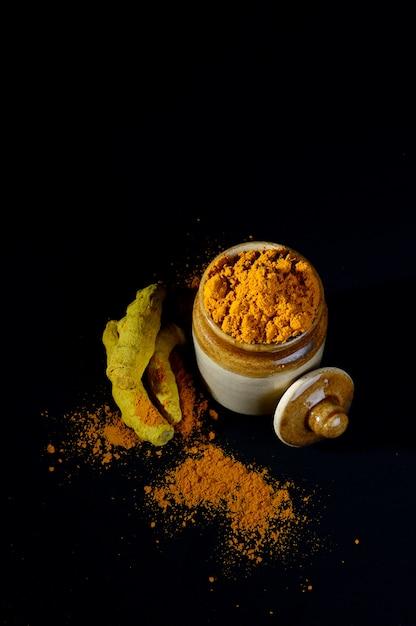 Kurkumapoeder in kleipot met wortels of blaft op zwarte oppervlakte Premium Foto