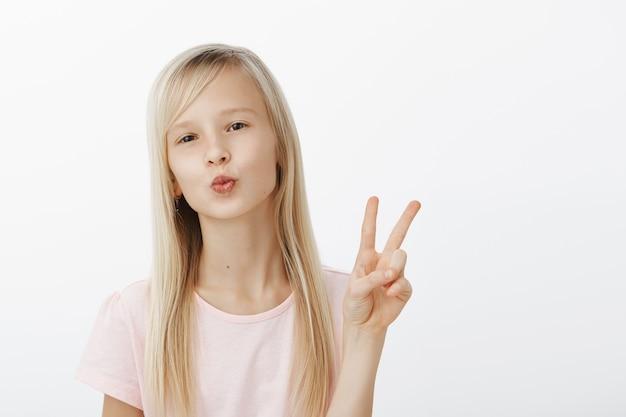 Kus aan mijn volgers, blijf op de hoogte. portret van modieus zelfverzekerd jong meisje met natuurlijk blond haar, lippen vouwen, kus blazen, vrede of overwinningsteken tonen, in goed humeur over grijze muur Gratis Foto