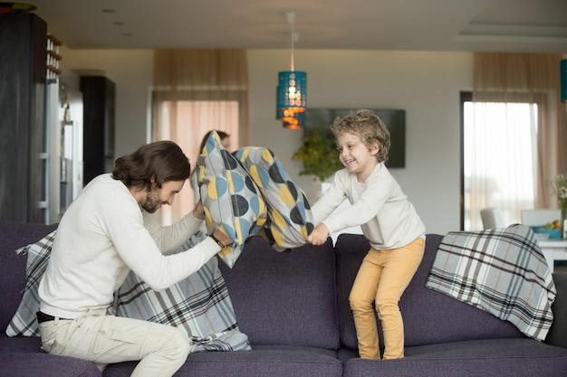 Kussengevecht tussen vader en zoontje in de woonkamer Gratis Foto