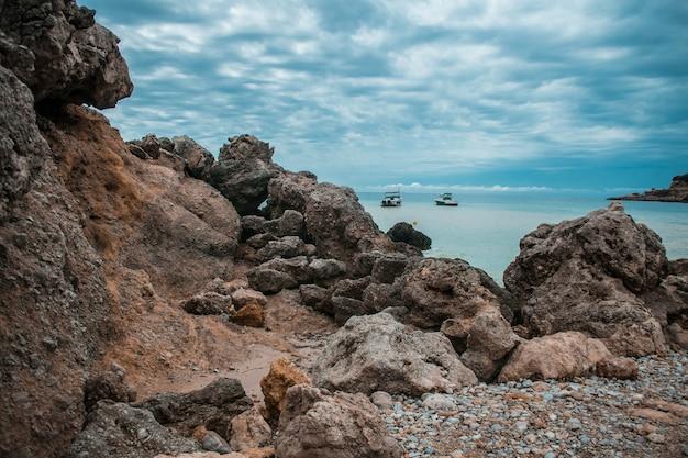Kustlijn vol rotsen, enkele schepen in de zee en de bewolkte hemel Gratis Foto
