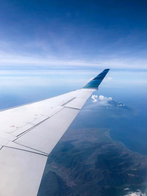Kustlijnmening van vliegtuigvenster op zonnige dag. vliegen en reizen concept Premium Foto