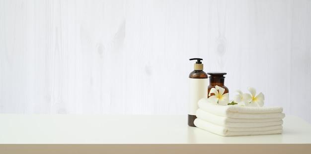 Kuuroord die met plumeriabloem en etherische oliefles plaatsen Premium Foto