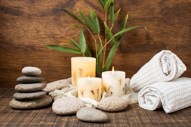 Kuuroordconcept met aangestoken kaarsen en handdoeken Gratis Foto