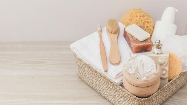 Kuuroordproducten met borstels en luffa in dienblad op houten achtergrond Gratis Foto