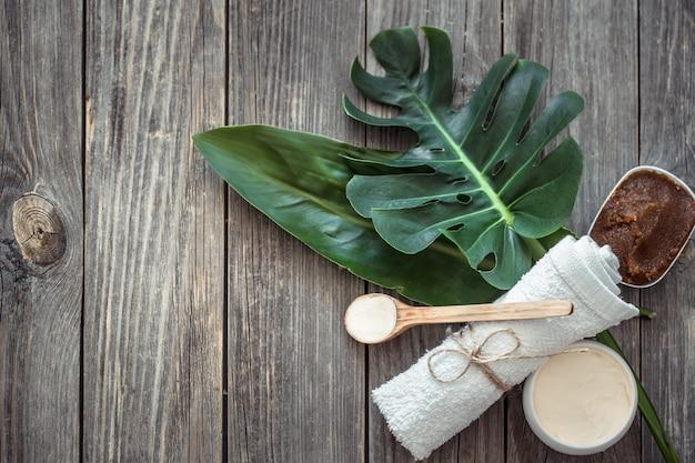 Kuuroordsamenstelling met handdoeken en tropisch blad op een houten muur. Gratis Foto