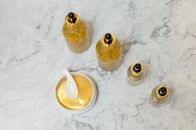 Kuuroordschoonheidsmiddelen op witte marmeren achtergrond van hierboven. schoonheid blogger. huidverzorgingsproducten. olie, creme, hydrogel gouden cosmetische ooglapje. Premium Foto