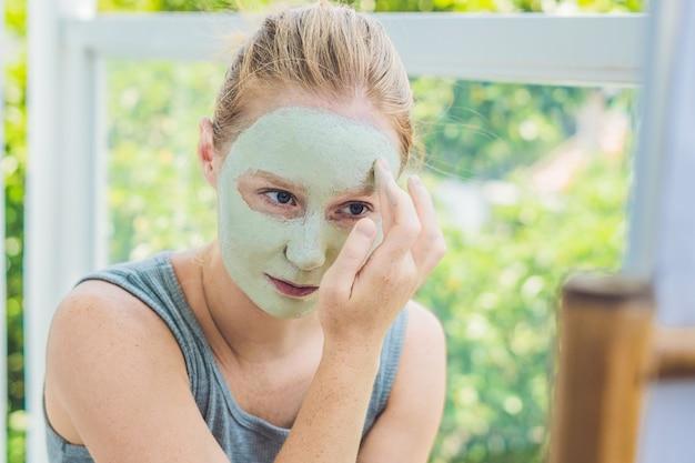 Kuuroordvrouw die gezichts groen kleimasker toepassen Premium Foto