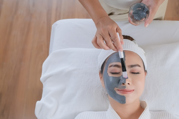 Kuuroordvrouw die gezichtskleimasker toepassen. schoonheidsbehandelingen. Premium Foto