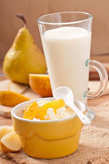 Kwark met perenjam in een kom en een glas melk Gratis Foto