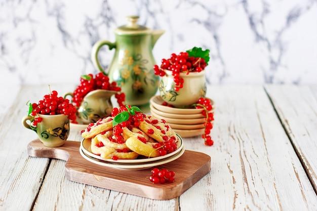 Kwarkkoekjesbroodjes met rode aalbessen op keramische plaat met vintage keramische thee of koffie set, theetijd, ontbijt, zomersnoepjes Gratis Foto