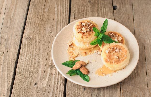 Kwarkpannekoeken met amandelenmunt en ahornsiroop in een beige plaat. Premium Foto