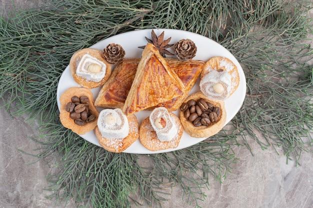 Kyata's, koekjes, lokums en dennenappels op een schaal op marmer. Gratis Foto