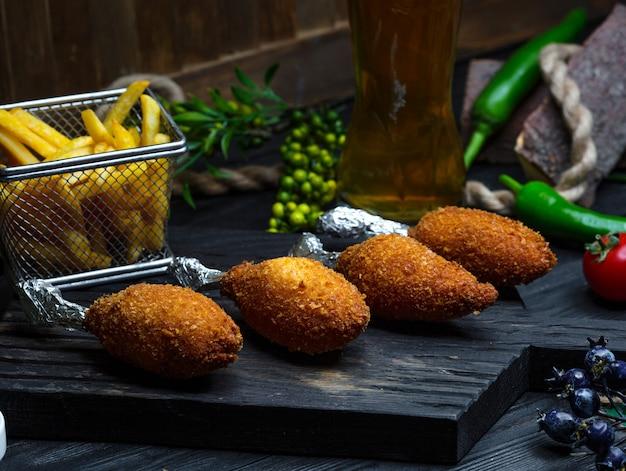 Kyiv cotletes met frietjes op houten bord Gratis Foto