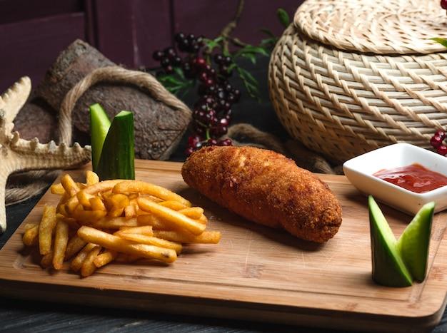 Kyot cotlete met frieten op houten raad Gratis Foto