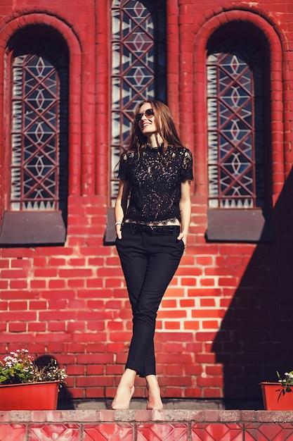 L stijlvol meisje, wandelen en poseren in zwarte kleding Premium Foto