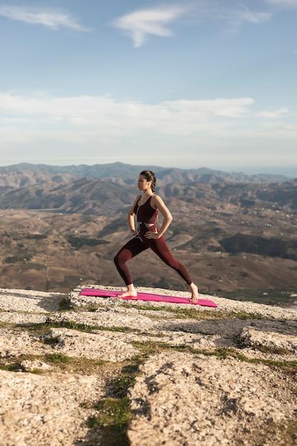 Laag hoek jong wijfje op berg die yoga doet Gratis Foto