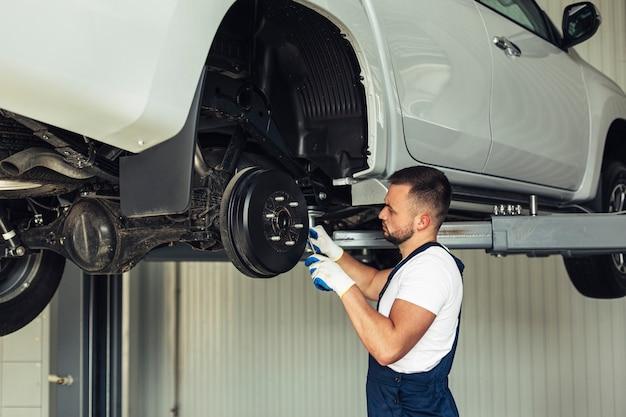 Laag hoek mechanisch mannetje dat autowielen controleert Gratis Foto