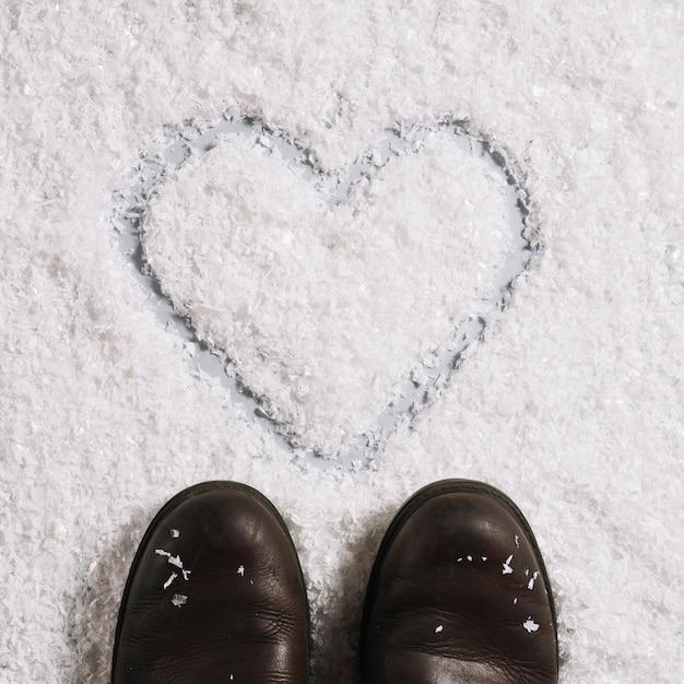 Laarzen dichtbij hart geschilderd op sneeuw Gratis Foto