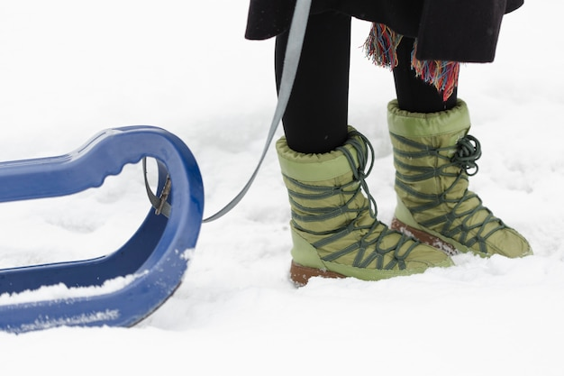 Laarzen in sneeuw en blauwe slee Gratis Foto