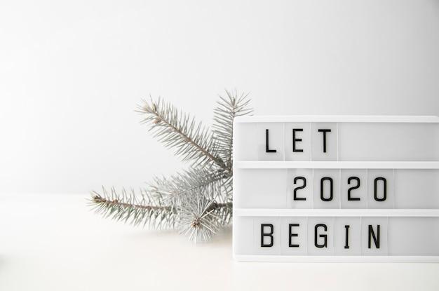 Laat 2020 nieuwjaar beginnen cijfers en zilveren kerstboombladeren Gratis Foto