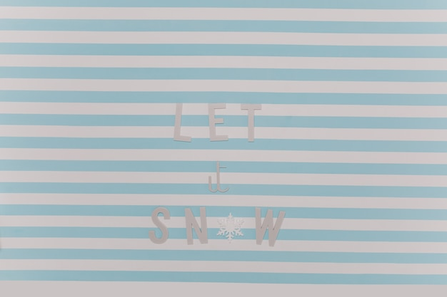 Laat het sneeuwen. mooie nieuwjaar winter inscriptie op wit en blauw gestreepte muur. Gratis Foto
