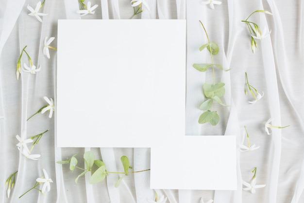 Laat takjes en jasminum auriculatum bloemen met trouwkaart op sjaal Gratis Foto