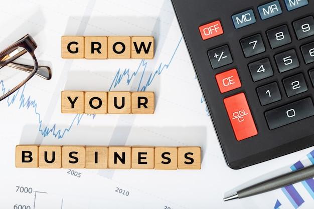 Laat uw bedrijfsconcept groeien. houten blokken met zin, rekenmachine en gedrukte tekens Premium Foto