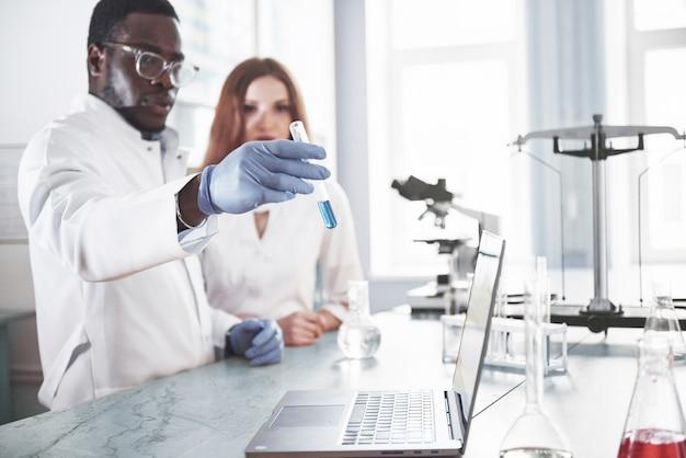Laboratoriumlaboratoria voeren experimenten uit in een chemisch laboratorium in transparante kolven. uitvoerformules. Gratis Foto