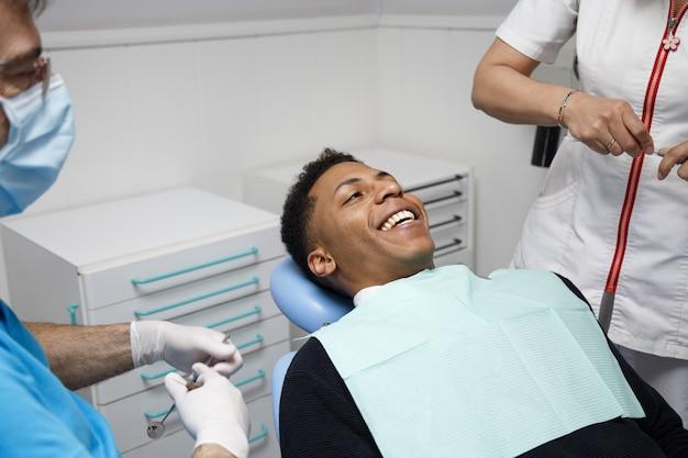 Lachen afro-amerikaanse man zit in de stoel van tandarts in de kliniek en de procedure met verpleegster voorbereiden. Premium Foto