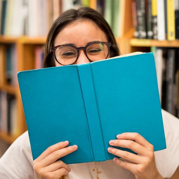 Lachen tiener schoolmeisje verbergen gezicht achter boek Gratis Foto