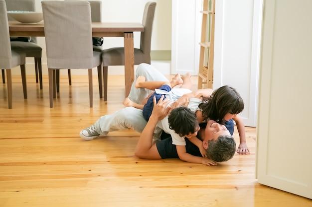 Lachen vader liggend op de vloer en schattige kinderen knuffelen. Gratis Foto