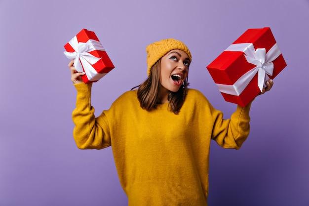 Lachend blij meisje in gele kledij genieten van wintervakantie. portret van spectaculaire vrouw voorbereiding nieuwjaar presenteert. Gratis Foto