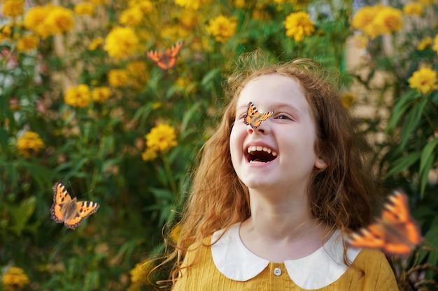 Lachend krullend meisje met een vlinder op zijn neus. Premium Foto