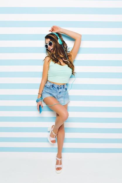 Lachend meisje in elegante hakken sandalen en stijlvolle zonnebril staande op één been poseren op gestreepte muur. portret van jonge dame lied in hoofdtelefoons luisteren en zingen, telefoon vasthouden. Gratis Foto