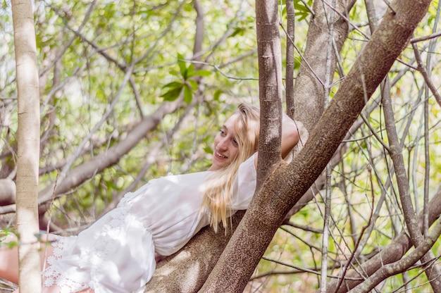 Lachend meisje liggend op een boom Gratis Foto