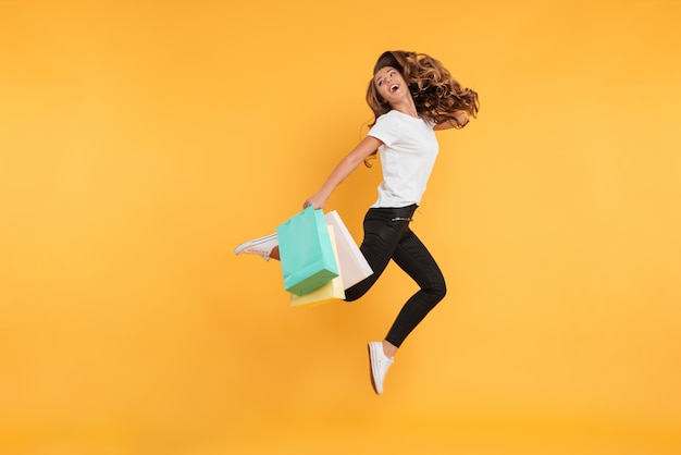 Lachend mooie jonge vrouw springen bedrijf boodschappentassen. Gratis Foto
