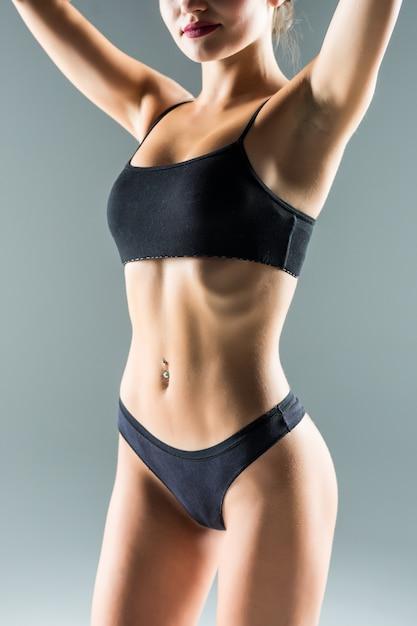 Lachend sportief meisje in het zwarte bikini stellen op grijze muur. foto van aantrekkelijk meisje met slank afgezwakt lichaam. schoonheid en lichaamsverzorging concept Gratis Foto