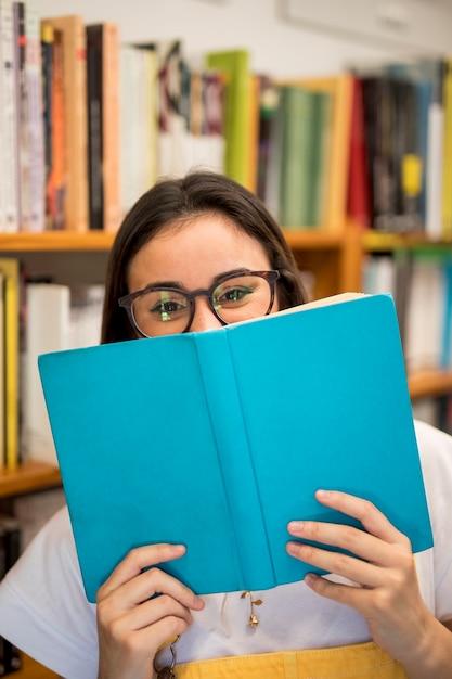 Lachend tienerschoolmeisje die gezicht behandelen met boek Gratis Foto