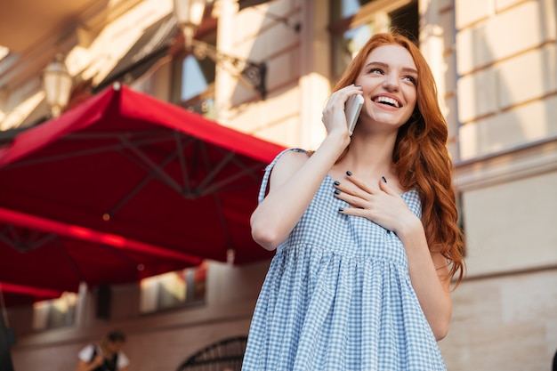Lachende aantrekkelijke vrouw met lang haar praten op mobiele telefoon Premium Foto