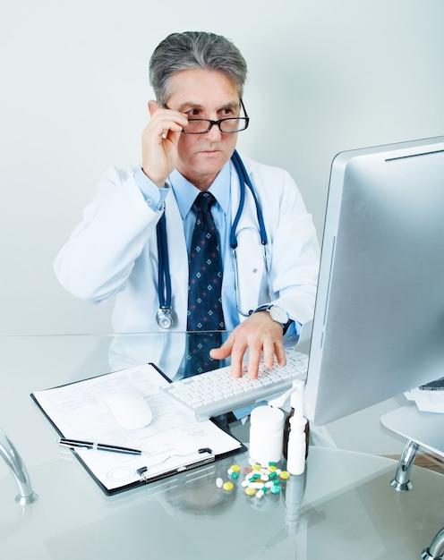 Lachende arts op zijn werkplek met computer, pillen, tabletten en patiëntgegevens geschiedenis Premium Foto