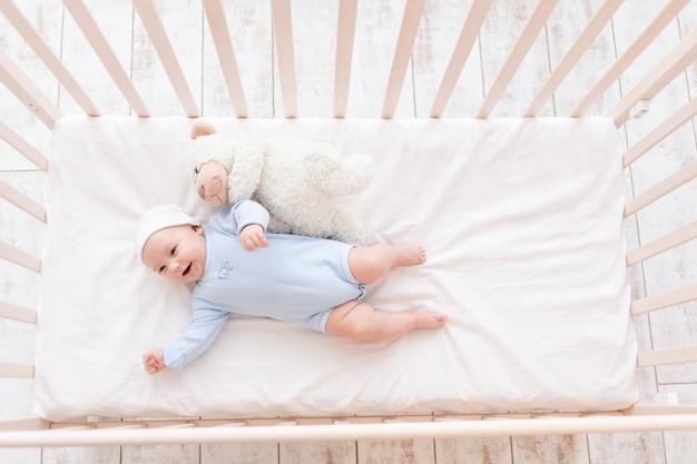 Lachende baby in wieg, schattige baby 3 maanden met teddybeer speelgoed, kinderen en geboorte concept Premium Foto