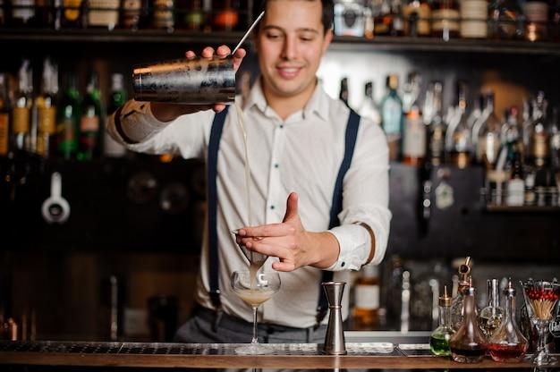 Lachende barman maakt een cocktail aan de bar staan Premium Foto
