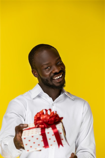 Lachende bebaarde jonge afro-amerikaanse man met een cadeau Gratis Foto