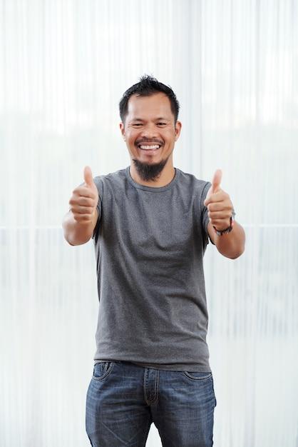 Lachende filipijnse mens die zich voor helder verlicht venster bevindt met zijn omhoog duimen Gratis Foto