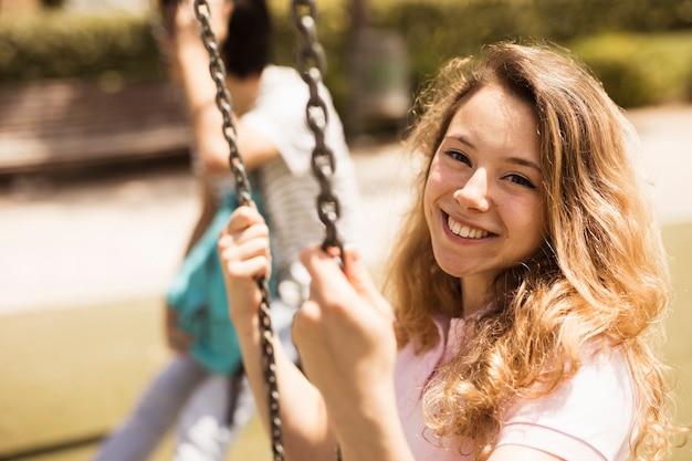 Lachende gelukkig schoolmeisje zittend op schommels Gratis Foto
