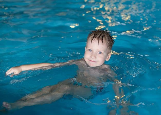 Lachende gelukkige jongen is zwemmen in het zwembad Premium Foto
