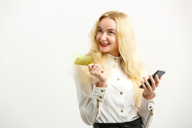 Lachende gelukkige vrouw met creditcard en mobiele telefoon tijdens het kijken naar camera Premium Foto