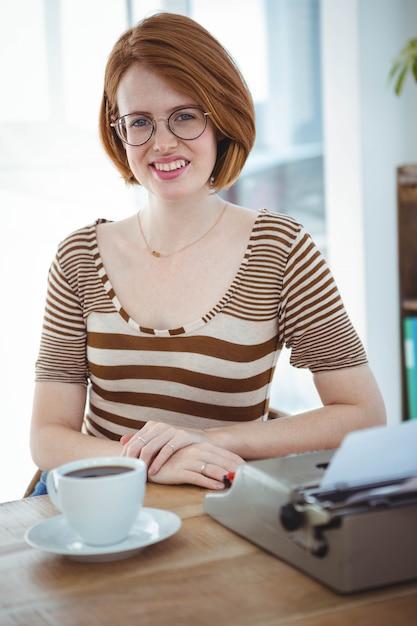 Lachende hipster vrouw aan een bureau met koffie en een typemachine Premium Foto