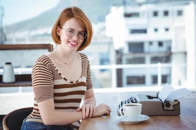 Lachende hipster vrouw zitten aan een bureau met een koffie en een typemachine Premium Foto