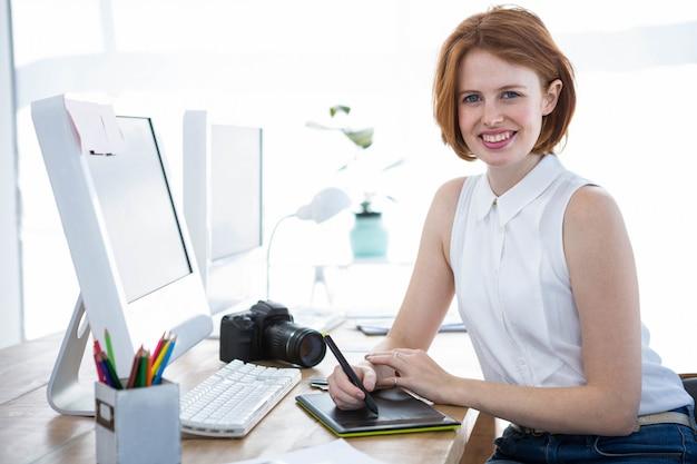 Lachende hipster zakenvrouw schrijven op een digitale tekentablet in haar kantoor Premium Foto